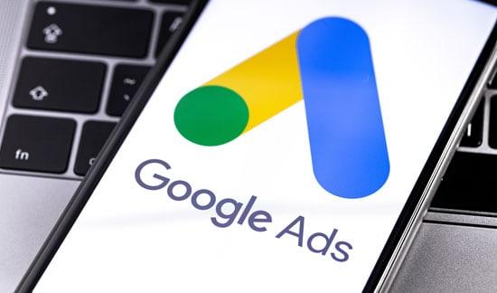 AdWords: KMU können Google Ads nutzen. Deshalb liegt ein Smartphone auf einer Computertastatur und zeigt den Schriftzug