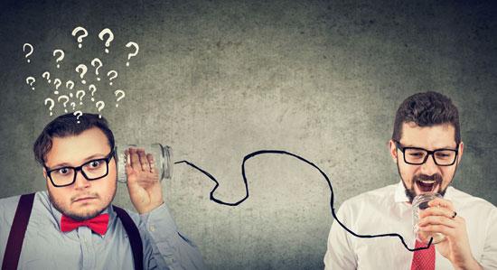 Ein Mann spricht in ein Dosentelefon. Ein anderer Mann schaut fragend und hat ganz viele Fragezeichen über dem Kopf. Das Bild steht sinnbildlich dafür, dass bei AdWords KMU ihren Interessenten sagen müssen, was sie tun sollen.