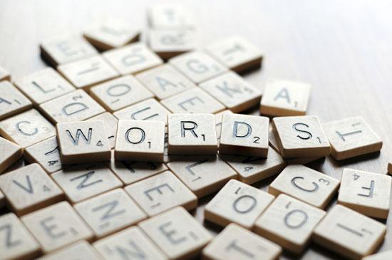 Scrabble-Steine formen das Wort words. Sie symbolisieren, wie ein freier Texter mit Worten spielt.