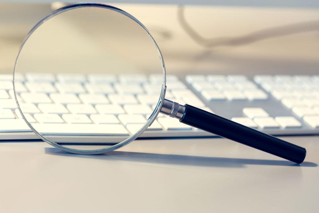 Online-Marketing: KMU gewinnen digitale Sichtbarkeit, die durch eine Lupe vor einer Computertastatur symbolisiert wird.