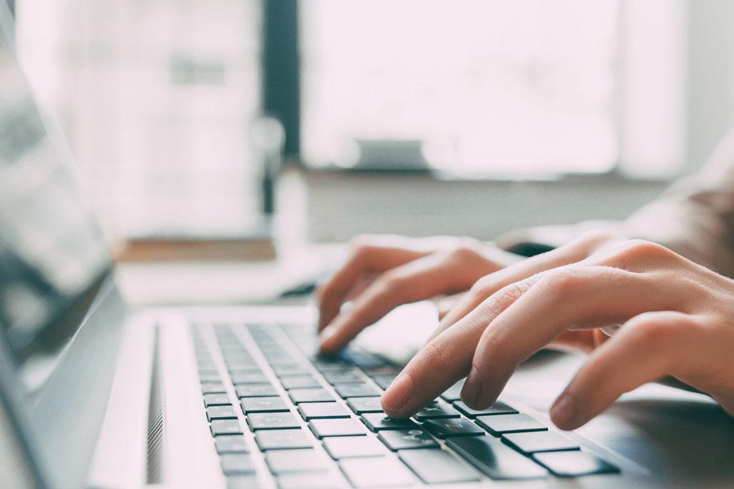 Online-Marketing: KMU können sich einen freien Texter zur Erstellung der Inhalte zu Hilfe nehmen. Man sieht seine tippenden Hände auf Computertastatur.