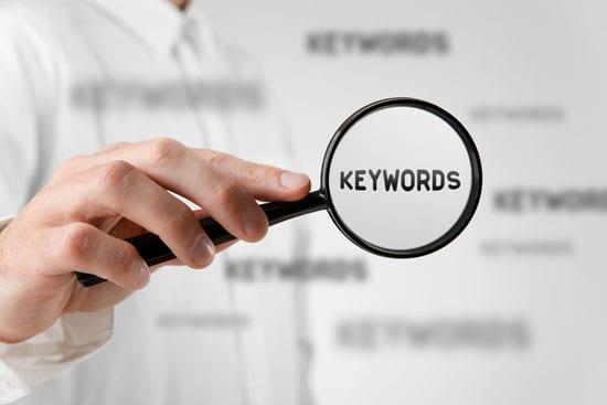 Das Wort Keywords wird durch eine Lupe vergrößert. Diese Symbolik soll die große Bedeutung von Keywords beim SEO für Blogs bildhaft darstellen.