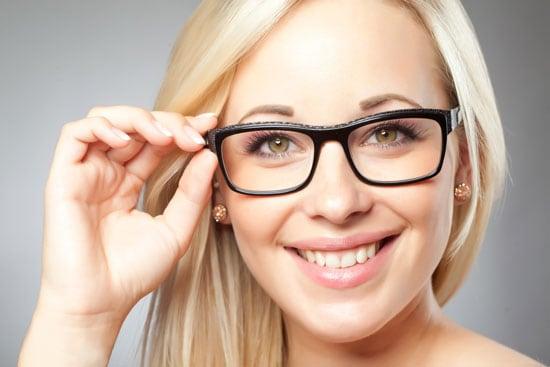 Frau setzt Brille auf und verdeutlicht damit die bessere Sichtbarkeit durch lokale Suchmaschinenoptimierung beim SEO für KMU.