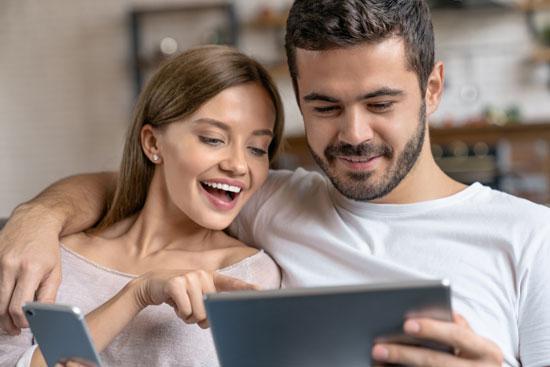 Ein Paar schaut auf ein Tablett, das der Mann in der Hand hält. Die Frau hält ein Smartphone in der Hand. Damit gilt für SEO: Mittelstand muss seine Inhalte für mobile Endgeräte optimieren.